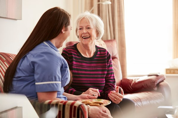 A member of staff is sat talking with a resident