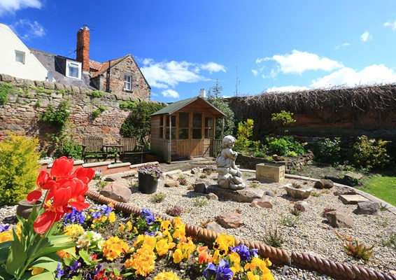 A stunning rockery in the garden with a summer house and bright flowers