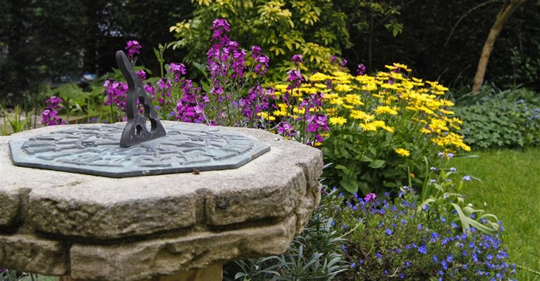 A sun dial in the garden surrounded by colourful flowers