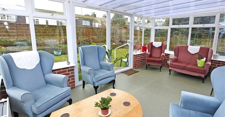 Bright conservatory overlooking the garden where residents can relax and socialise