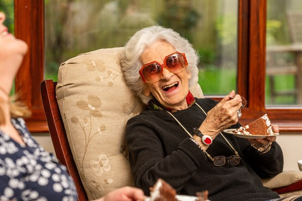 Smiling resident enjoys a laugh whilst eating her chocolate cake