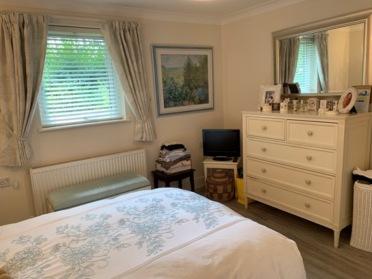A large bedroom with a chest of draws, tv and bed