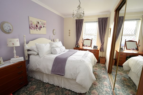 Double bed in a lilac bedroom