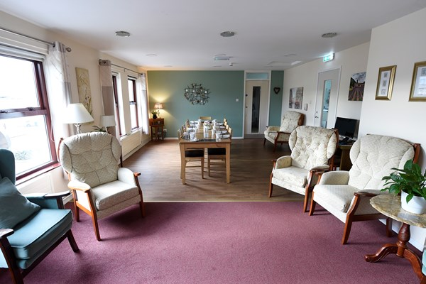The lounge area with comfortable seating and the dining table in the background
