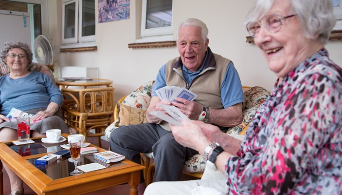 Residents sitting around a coffee table enjoying playing cards together