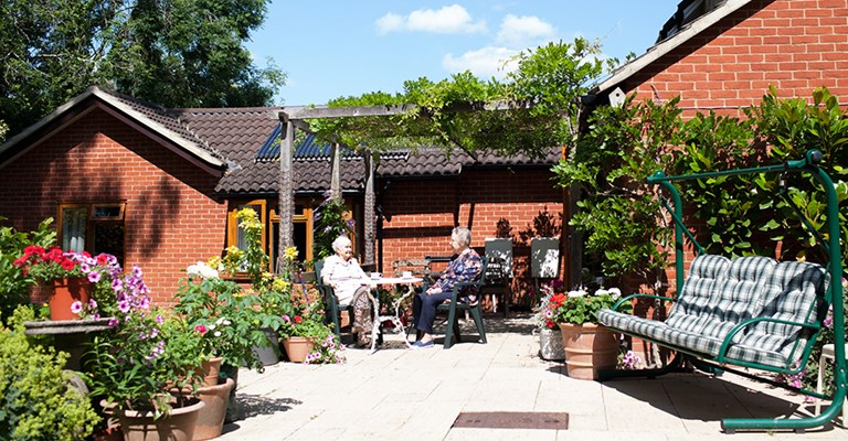 Residents enjoying the sun on the patio in the beautiful garden at Roundhay