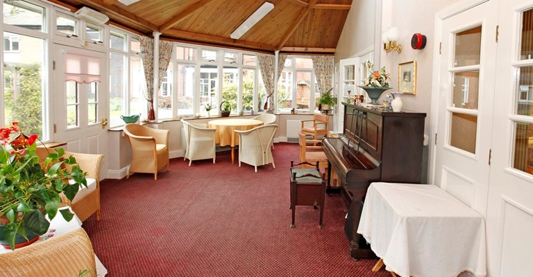 Large bright conservatory area with tables and a piano