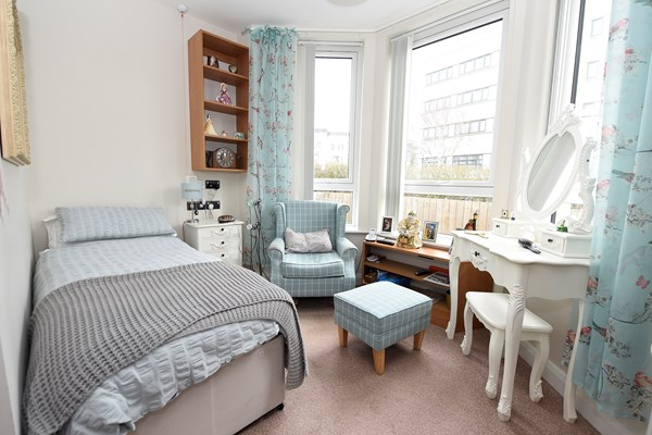 A modern bedroom with duck egg blue furniture and curtains
