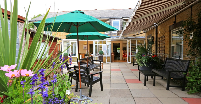 The patio with bright flowers and parasols