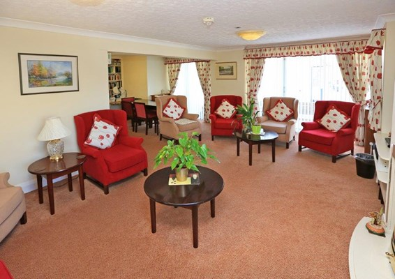Large bright lounge with red and cream chairs