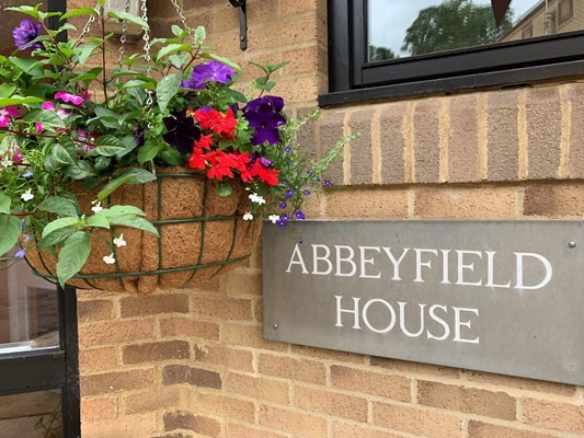 Abbeyfield House sign next to hanging basket at the front of the house