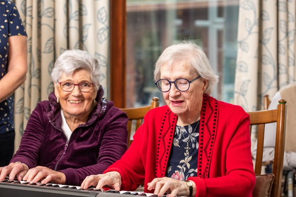 Smiling and happy residents play on the keyboards together at Culver House