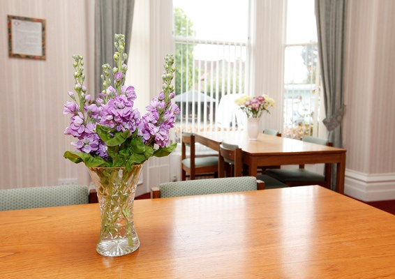 Table with purple flowers in a vase
