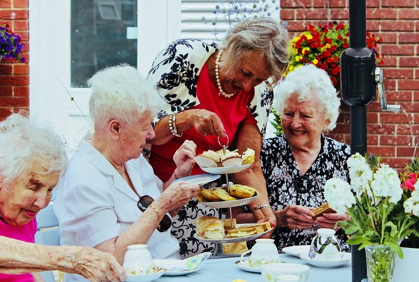 Residents are sat enjoying afternoon tea outside