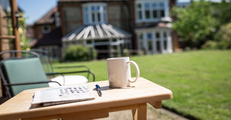 Wordsearch and coffee set up on table in the sunny garden at Gardener House