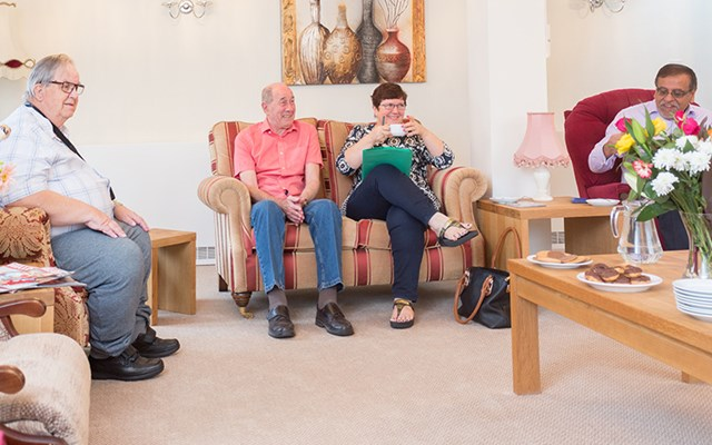 Residents sitting together enjoying tea and biscuits in the communal lounge at Abbeyfield House, Basildon