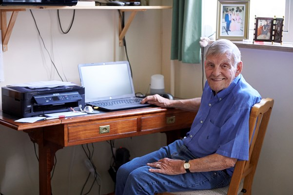 Smiling resident using laptop in room at Westall House