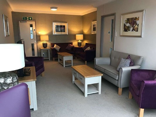 A modern lounge area with purple and grey chairs