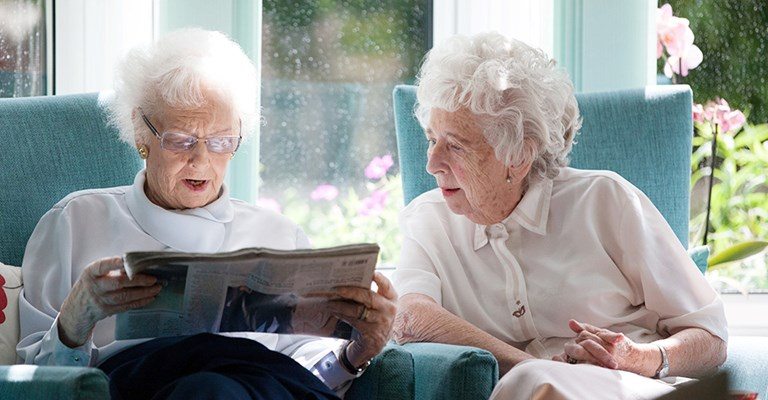 Residents sitting looking at newspaper together at Roundhay