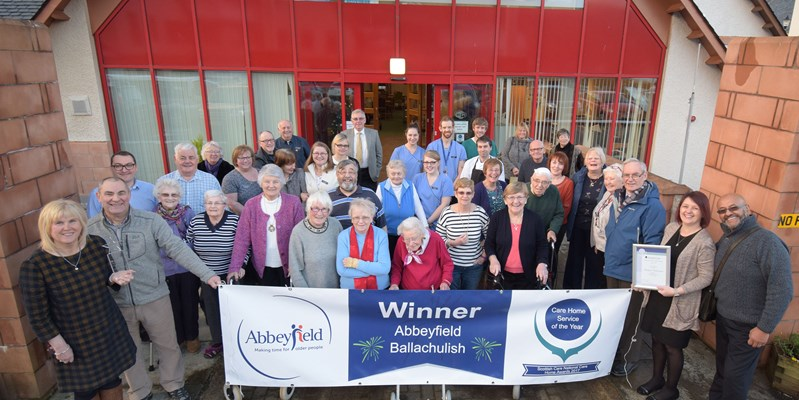 Residents and staff stand behind a Winner banner