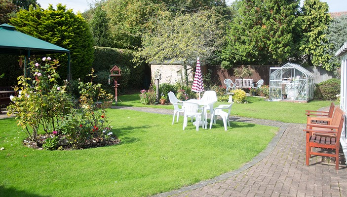 Beautiful garden with benches, table and chairs and greenhouse at Abbeyfield House, Basildon