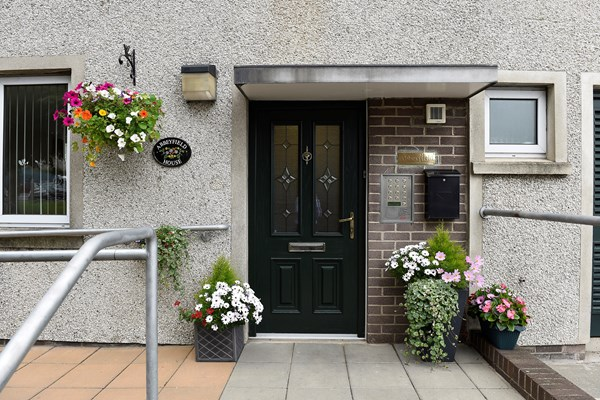 The entrance door to the house with bright plants in pots and hanging baskets