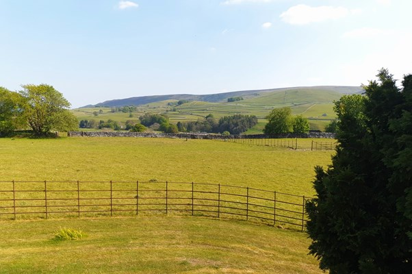 The view outside the house, vast countryside behind a small fence