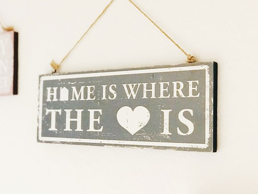Sign on the wall which says Home is where the heart is