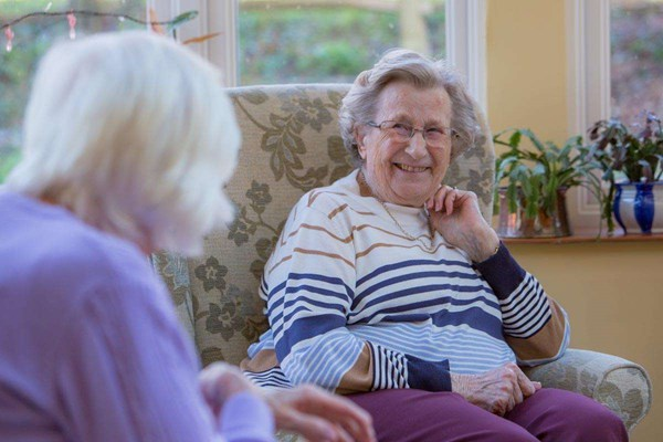 Two residents at Abbeyfield House, Alfriston sitting in chairs having a chat and smiling